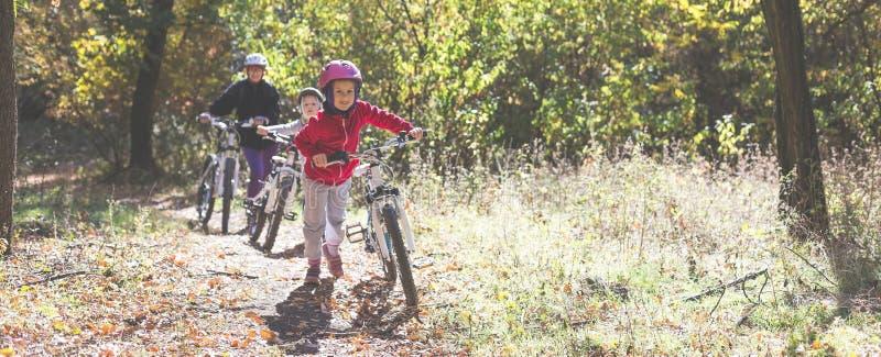 La madre y dos hijas con las bicis van ascendentes en el bosque del otoño foto de archivo libre de regalías