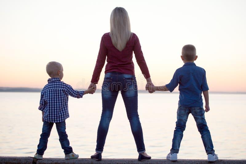La madre y dos hijos caminan en la 'promenade' y miran la puesta del sol foto de archivo libre de regalías