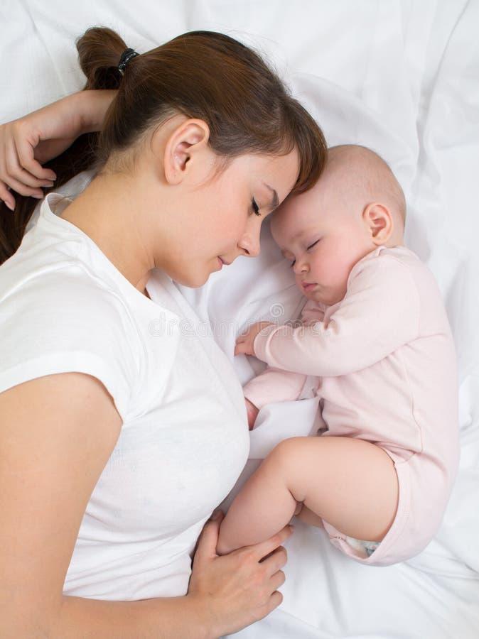 La madre y el bebé duermen juntos fotos de archivo