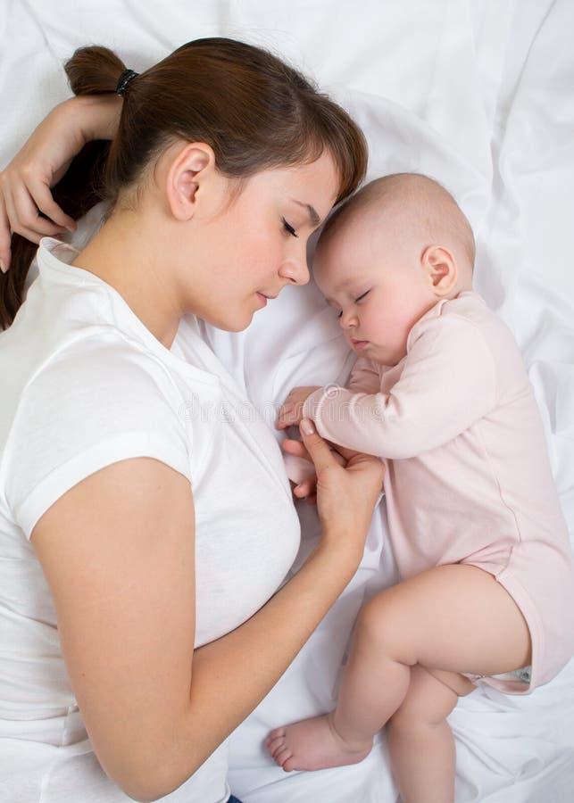 La madre y el bebé duermen juntos foto de archivo