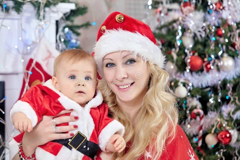 La madre y el bebé en sombreros del ` s de Papá Noel de la Navidad acercan al árbol de navidad en casa fotografía de archivo
