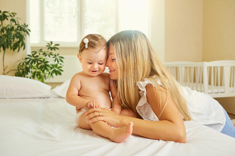 La madre y el bebé en un pañal juegan el abrazo en una cama dentro imágenes de archivo libres de regalías