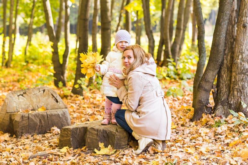 La madre y el bebé felices de la familia ríen con las hojas en otoño de la naturaleza imagen de archivo