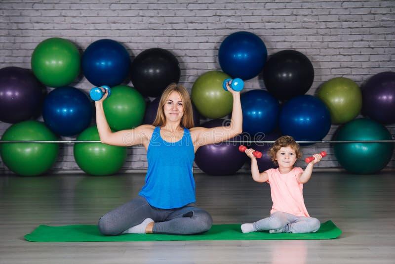 La madre y el bebé hacen ejercicios juntos en el gimnasio fotos de archivo