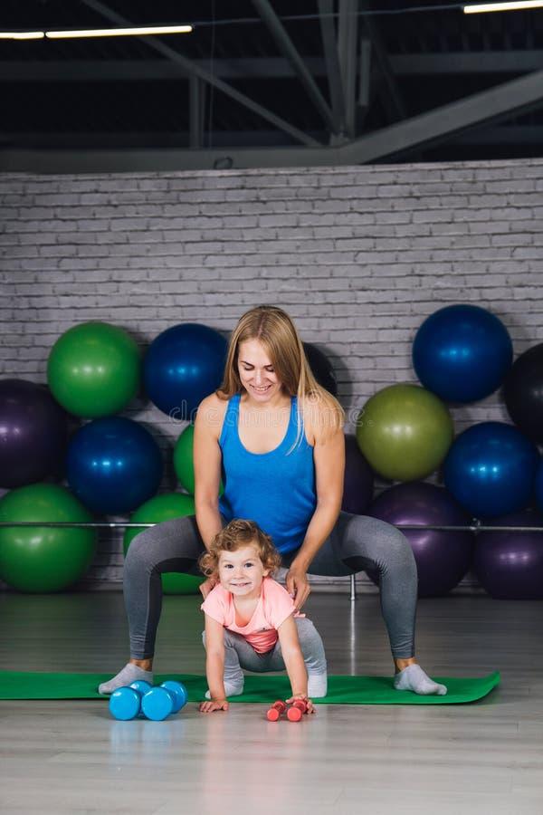 La madre y el bebé hacen ejercicios juntos en el gimnasio foto de archivo