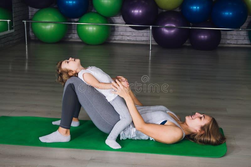 La madre y el bebé hacen ejercicios juntos en el gimnasio fotos de archivo libres de regalías