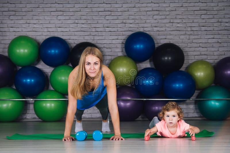 La madre y el bebé hacen ejercicios juntos en el gimnasio fotografía de archivo libre de regalías