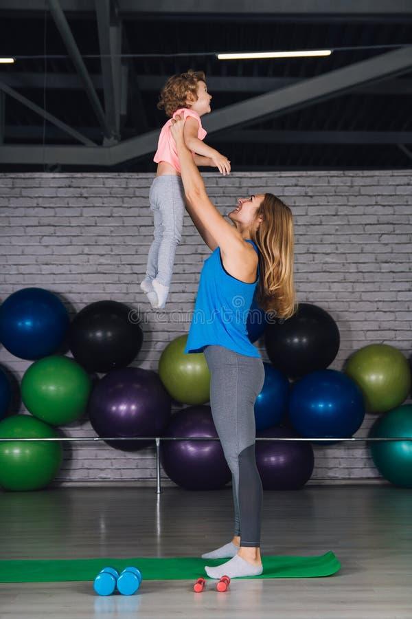 La madre y el bebé hacen ejercicios juntos en el gimnasio foto de archivo libre de regalías
