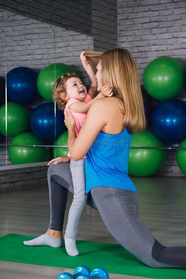 La madre y el bebé hacen ejercicios juntos en el gimnasio imagen de archivo