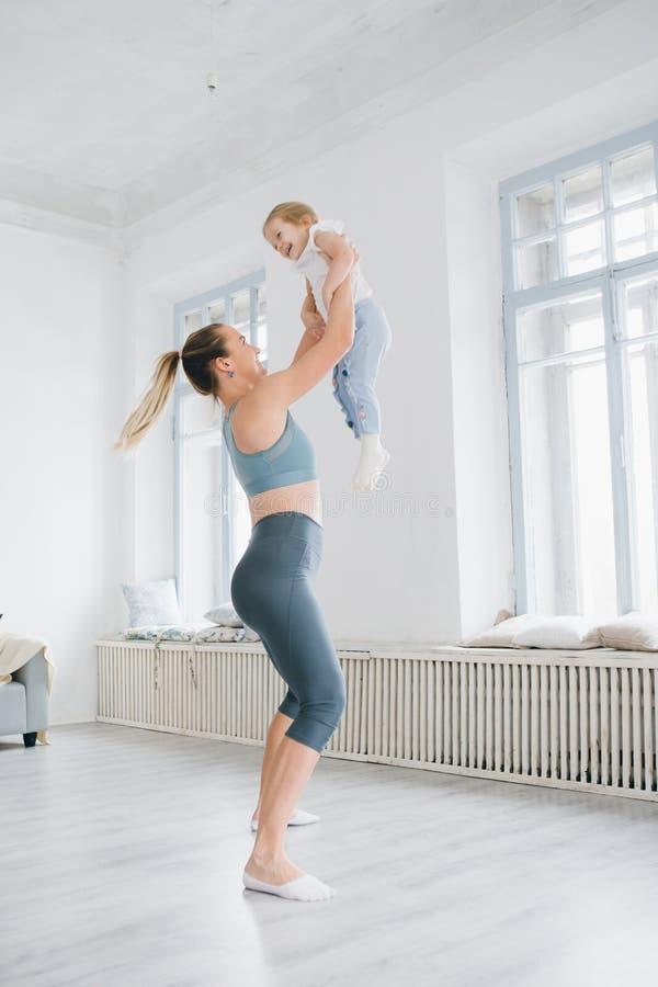 La madre y el bebé hacen ejercicios juntos en el gimnasio fotografía de archivo