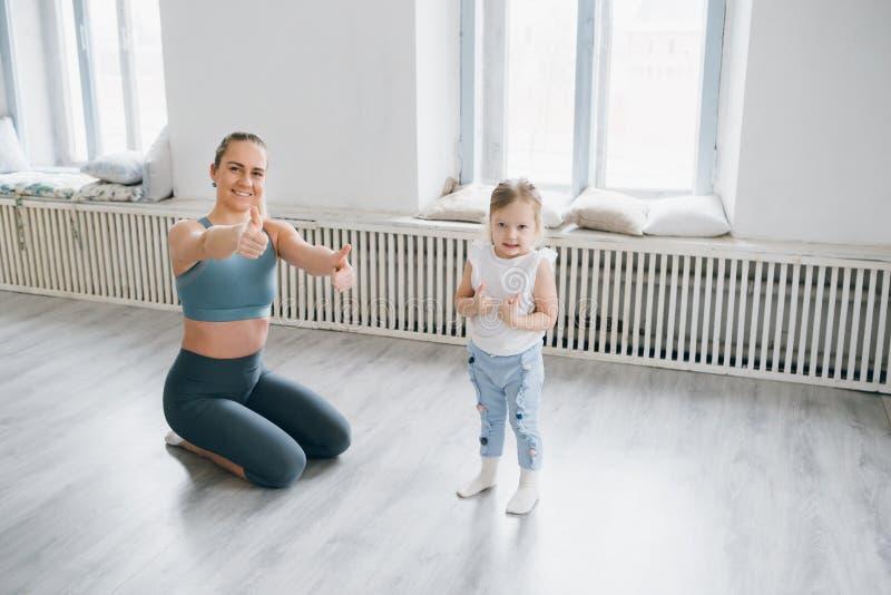 La madre y el bebé hacen ejercicios juntos en el gimnasio imágenes de archivo libres de regalías