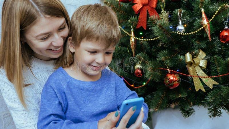 La madre y el hijo con el teléfono móvil se están sentando juntos cerca del árbol de navidad fotos de archivo