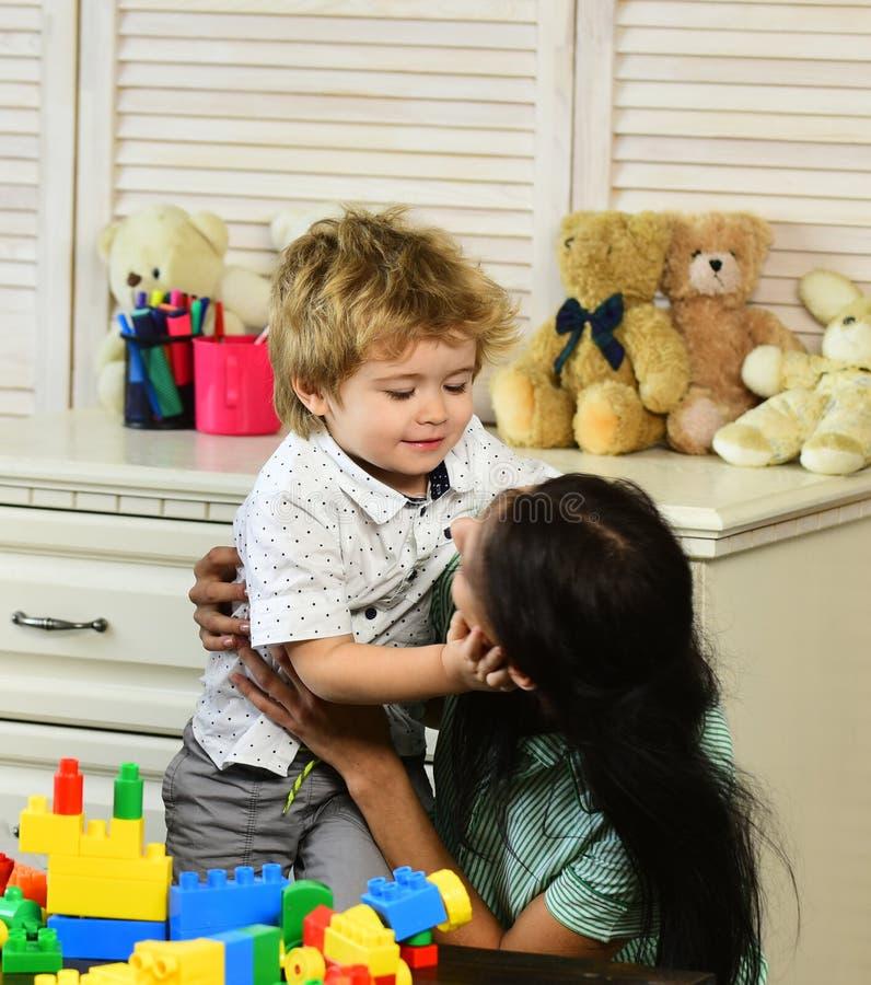 La madre y el hijo con las caras felices hacen construcciones de los bloques fotografía de archivo