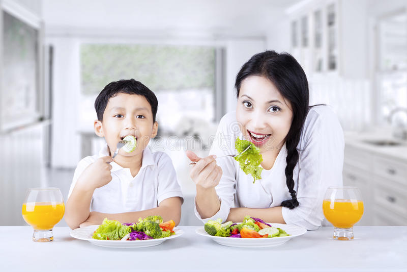 Familia asiática eathing la ensalada sana en casa fotos de archivo