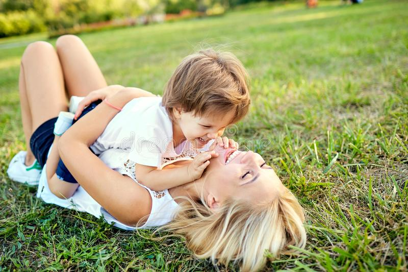La madre y el hijo están jugando el abrazo en la hierba en el parque foto de archivo