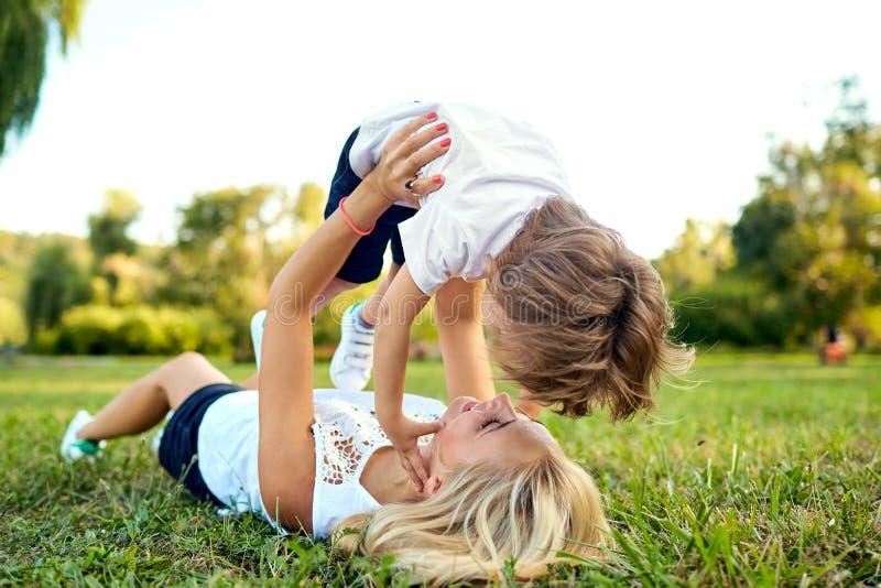 La madre y el hijo están jugando el abrazo en la hierba en el parque foto de archivo libre de regalías