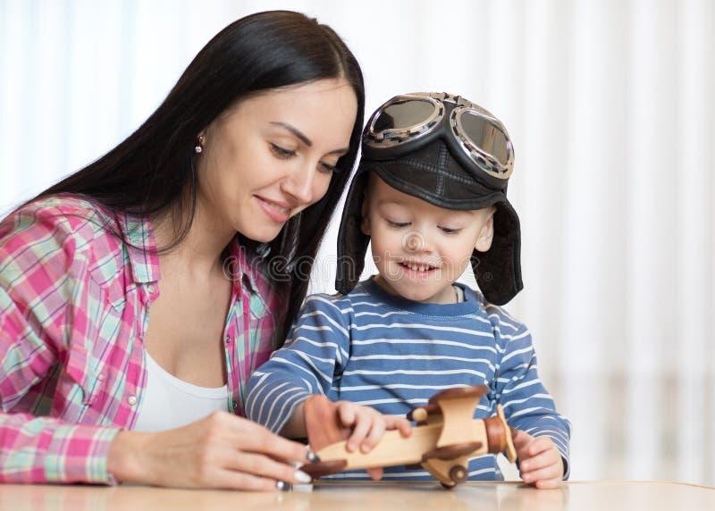 La madre y el hijo están jugando con los aviones de madera imagenes de archivo