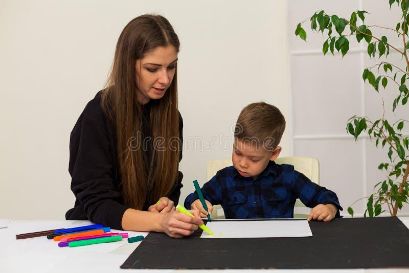 La madre y el hijo joven dibuja una imagen en la tabla foto de archivo libre de regalías