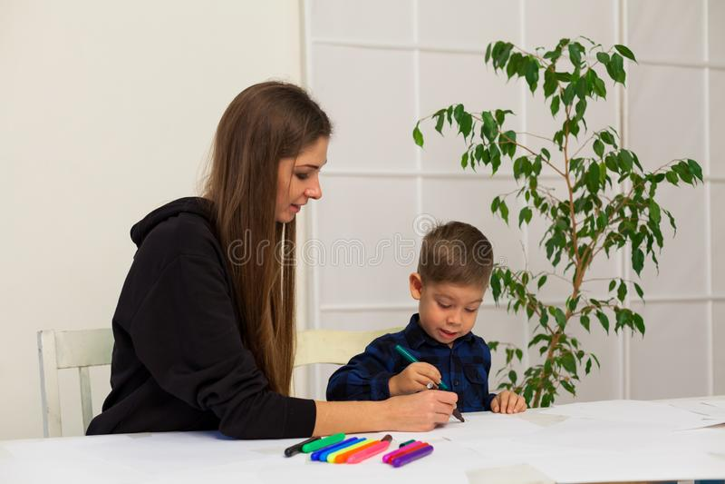 La madre y el hijo joven dibuja una imagen en la tabla imágenes de archivo libres de regalías