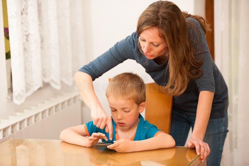 La madre y el hijo juega en el teléfono elegante en la tabla fotos de archivo libres de regalías