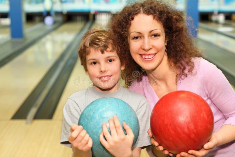 La madre y el hijo mantienen bolas club del bowling imagen de archivo