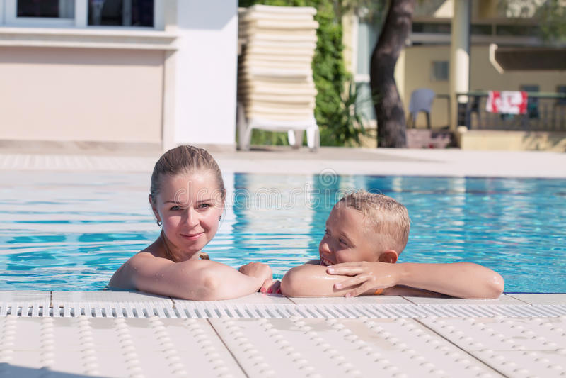 La madre y el hijo se divierten al lado de una piscina foto de archivo