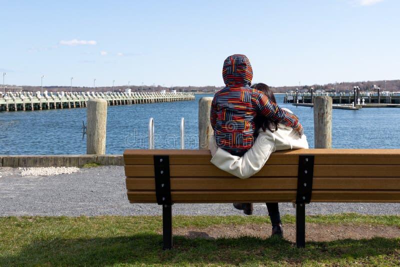 La madre y el hijo se sientan en una silla de madera que mira el lago imagenes de archivo