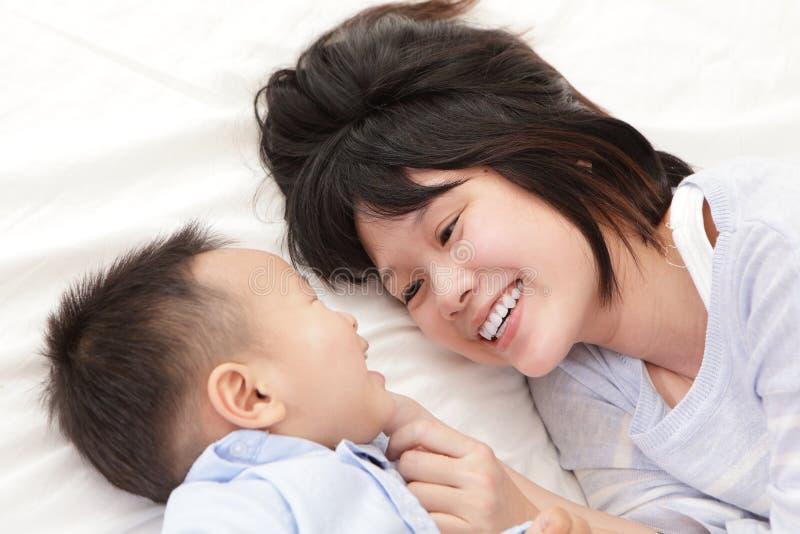 La madre y el hijo sonríen y se miran imágenes de archivo libres de regalías