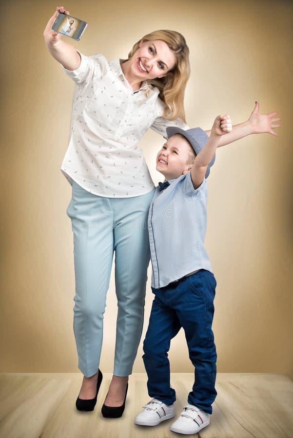 La madre y el hijo toman una foto del selfie en su teléfono móvil Elegante, de moda, moderno imagen de archivo