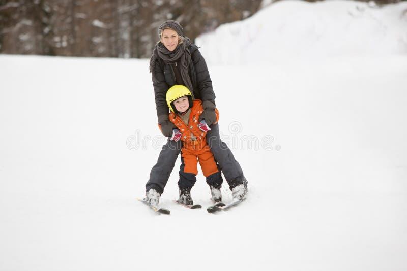 La madre y el niño aprenden esquiar juntos fotos de archivo