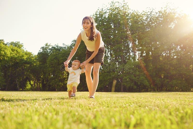 La madre y el niño están caminando en el parque en la puesta del sol fotos de archivo