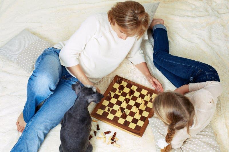 La madre y el niño están jugando a ajedrez mientras que pasa el tiempo junto en casa imagen de archivo libre de regalías