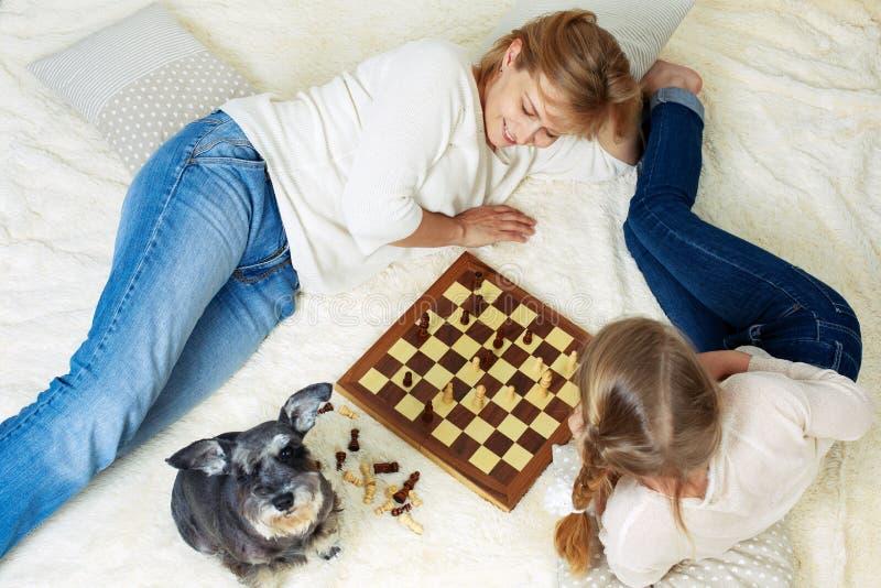 La madre y el niño están jugando a ajedrez mientras que pasa el tiempo junto en casa fotografía de archivo