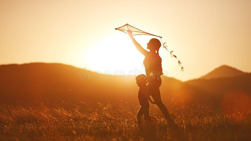 La madre y el niño felices de la familia corren en prado con una cometa en summe