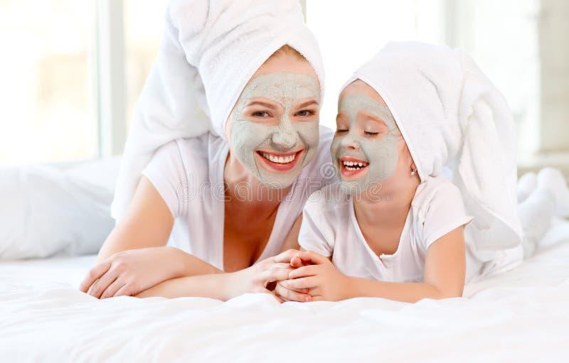La madre y el niño felices de la familia hacen que la cara pela la máscara imágenes de archivo libres de regalías