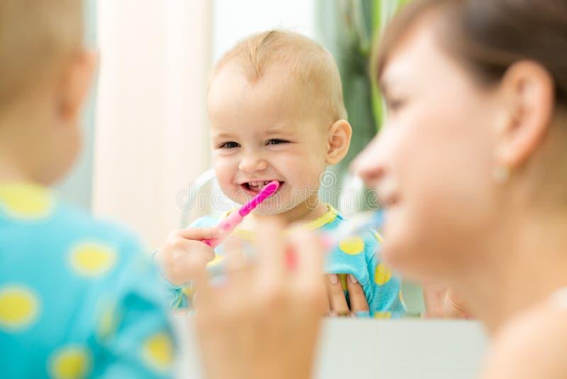 La madre y el niño miran el espejo durante los dientes fotografía de archivo libre de regalías