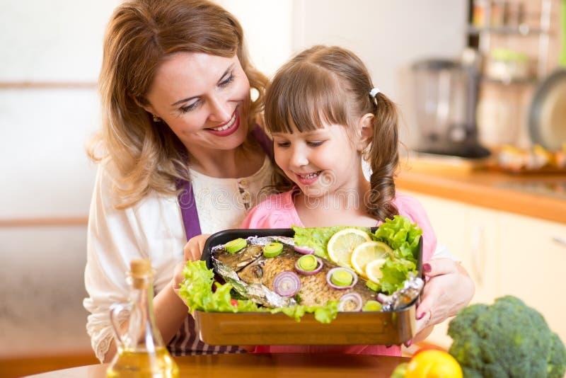 La madre y el niño muy miran el plato preparado de imagen de archivo