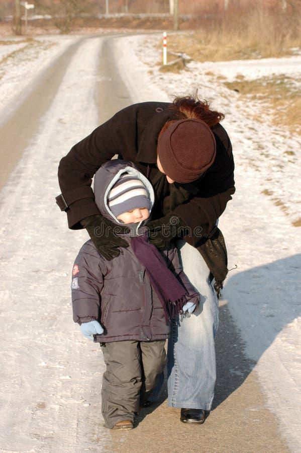 La madre y el niño recorren en un camino del invierno. imagen de archivo