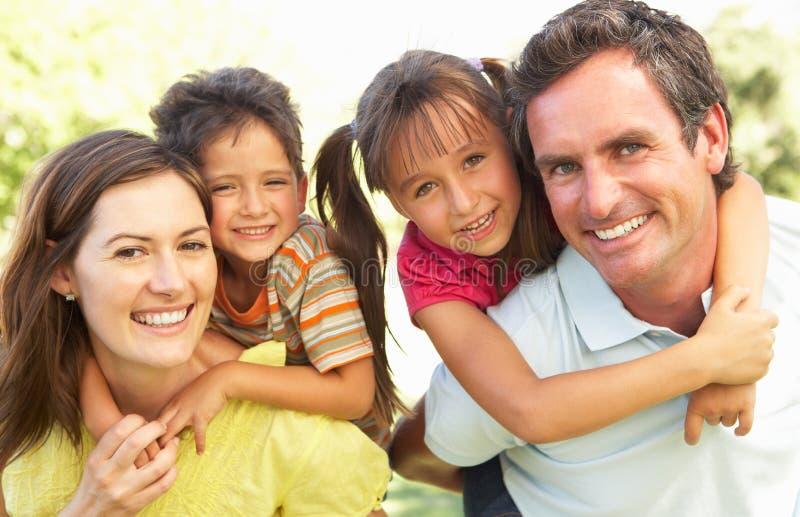 La madre y el padre que dan a niños llevan a cuestas fotografía de archivo