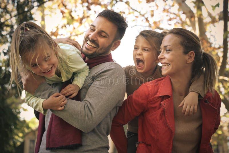 La madre y el padre tienen juego con los niños En el movimiento foto de archivo libre de regalías