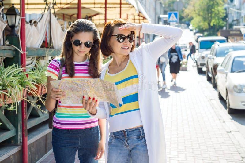 La madre y la hija adolescente en la calle de la ciudad miran el mapa Familia que viaja fotos de archivo libres de regalías