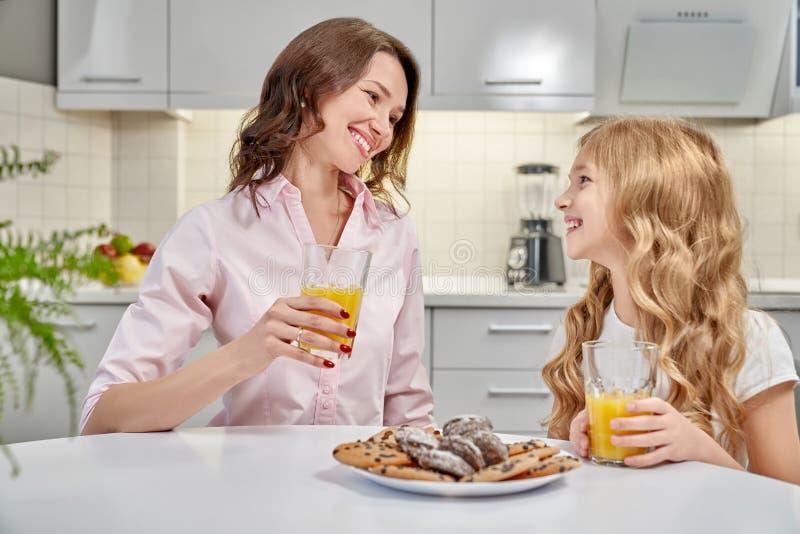 La madre y la hija beben el zumo de naranja y las galletas de la consumición imagen de archivo libre de regalías