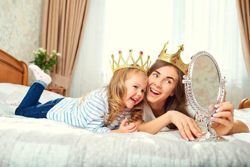 La madre y la hija con las coronas en la cabeza están jugando en el b fotografía de archivo
