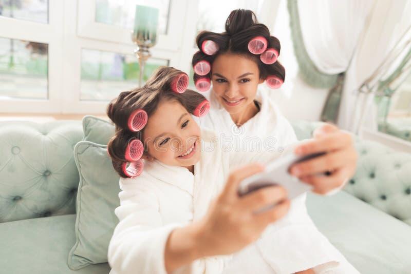 La madre y la hija en las albornoces blancas se están sentando en el sofá Tienen bigudíes en su pelo foto de archivo