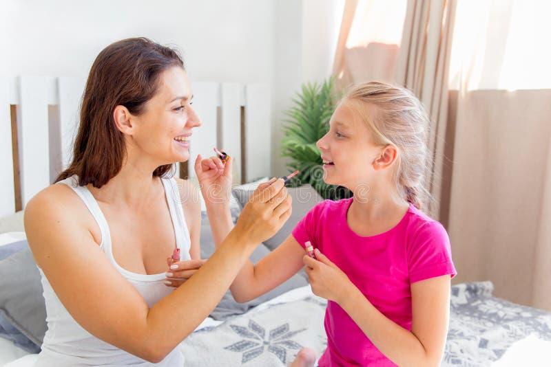 La madre y la hija están haciendo componen y se están divirtiendo en casa foto de archivo libre de regalías