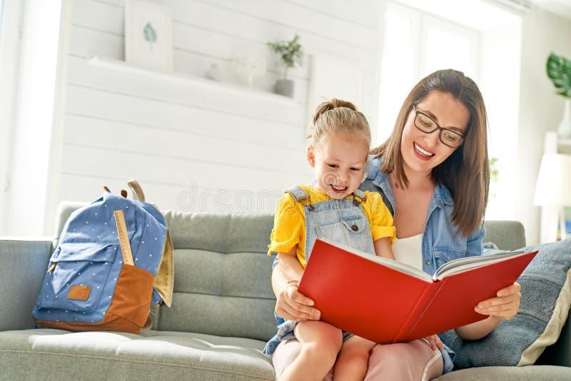 La madre y la hija est?n leyendo un libro foto de archivo libre de regalías