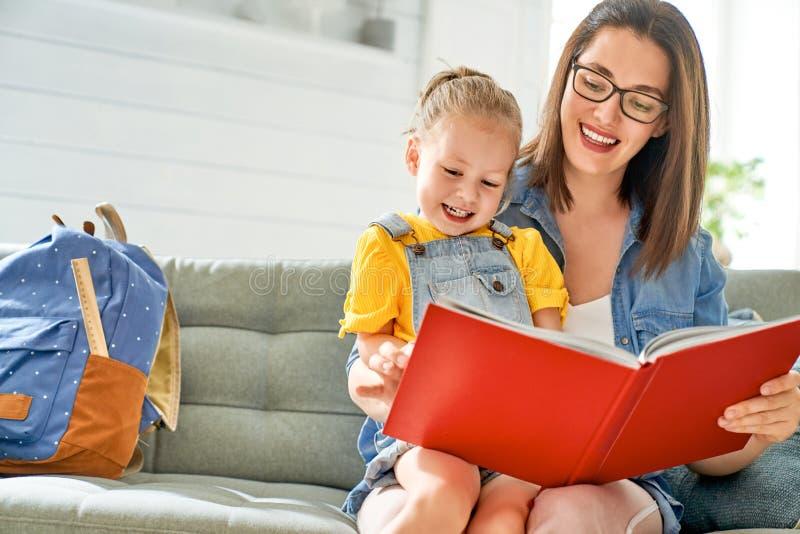 La madre y la hija est?n leyendo un libro imagen de archivo libre de regalías