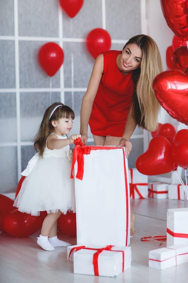 La madre y la hija felices analiza los regalos el día del ` s de la tarjeta del día de San Valentín foto de archivo