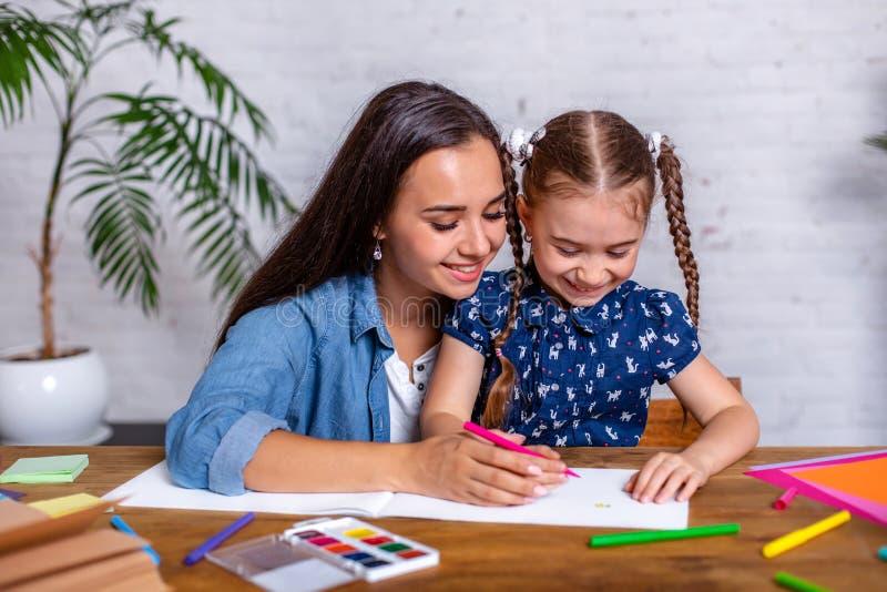 La madre y la hija felices de la familia juntas dibujan con los marcadores fotografía de archivo libre de regalías