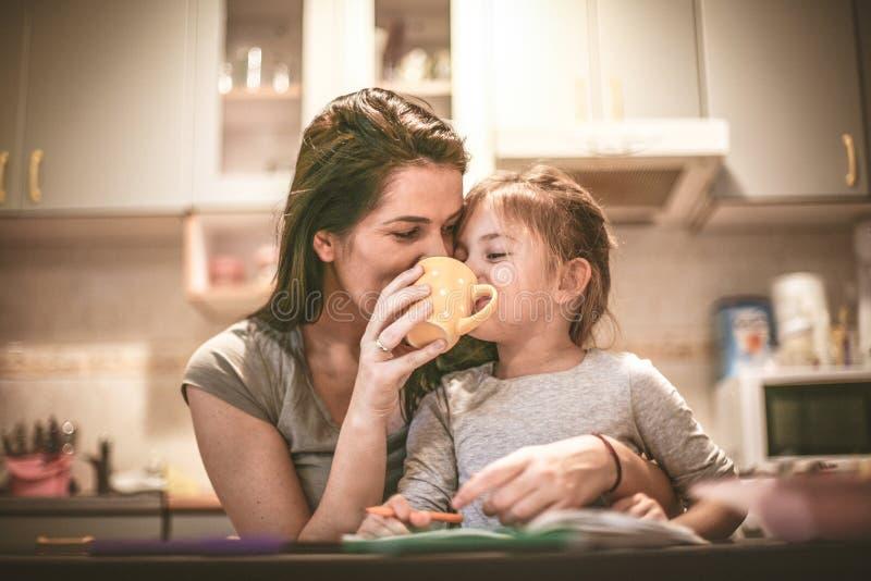 La madre y la hija gozan juntas En casa cocina fotos de archivo